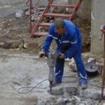 Man using jackhammer on sidewalk