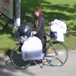 Woman carrying a lot of things on the bike