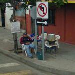 Man on corner with food in chair for sale