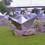 5 paper boats sculptures in a roundabout