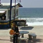 Man playing guitar by the beach in Tijuana
