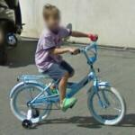 Boy on a bicycle with training wheels (StreetView)
