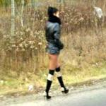 Long-legged hooker walking on the road