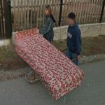 Carrying the bed on a wheelbarrow (StreetView)