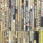 Wall covered with old hockey sticks