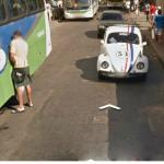 Guy takes a leak against side of bus, while Herbie the Love Bug watches