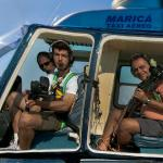 Photographers aboard a helicopter in flight