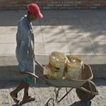 Guy carrying two buckets of water on a wheelbarrow