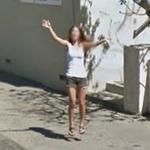 Woman greeting Google car with a jump