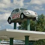 VW Beetle on sign poles