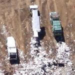 Trucks unloading trash at a garbage dump