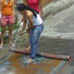 Woman washing a carpet (StreetView)