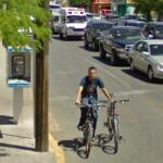 Man riding a bike and guiding another with an ambulance in the background (StreetView)