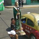 Man carrying a religious statue (StreetView)