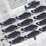 Bakers dozen of Helicopters waiting to be shipped out (Google Maps)