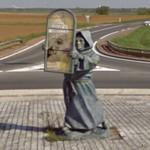 Monk with stained glass window in a roundabout (StreetView)