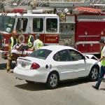 Damaged car and person on a stretcher (StreetView)