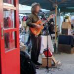 Man playing a guitar (StreetView)