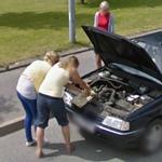 Women trying to fix the car