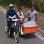 Guy on motorcycle with women on a sidecar
