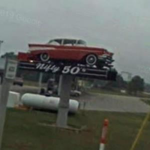 1957 Chevy on a sign pole (StreetView)