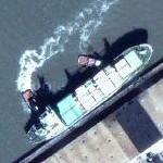 Tugs pushing a cargo ship in to dock (Google Maps)