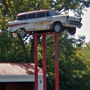 Old Chevrolet station wagon on a sign pole (StreetView)