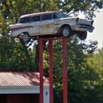 Old Chevrolet station wagon on a sign pole