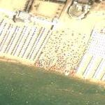 Cabanas and sunbathers on a crowded beach (Google Maps)